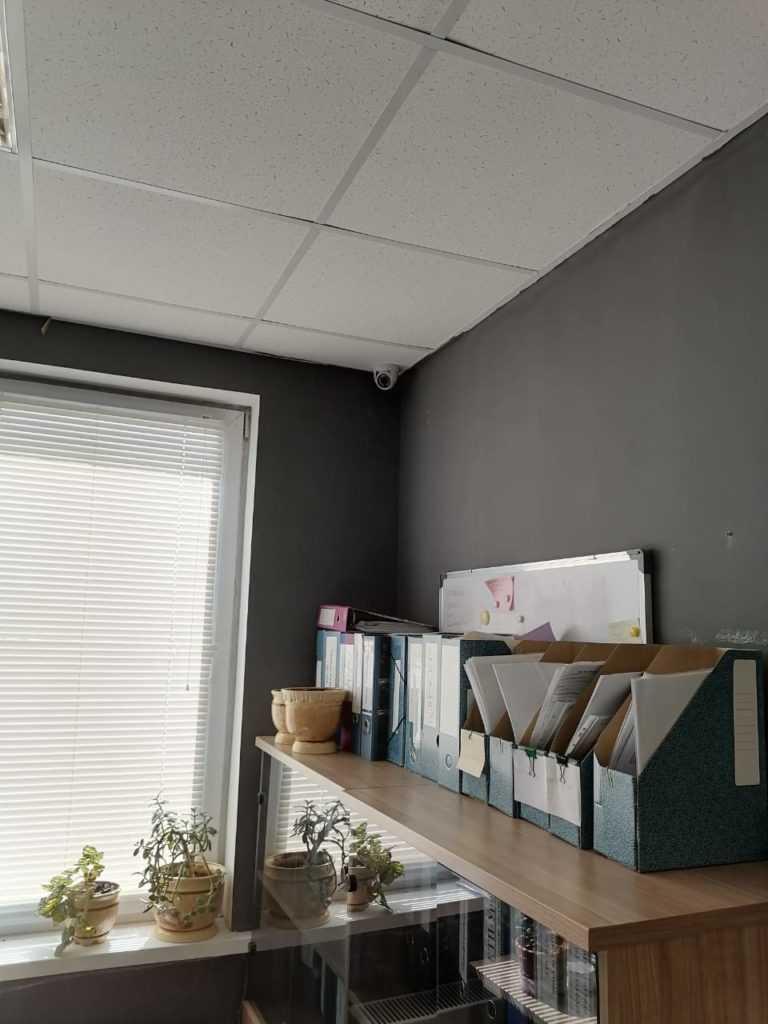 Камера в углу стены офиса